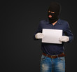 Man wearing a robber mask showing a blank paper