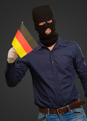 Man wearing robber mask and holding flag