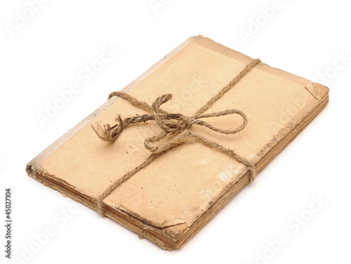 Old book tied up by a rope isolated on a white background