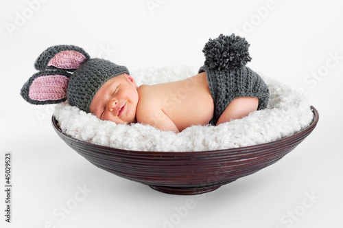 smiling newborn baby boy wearing a gray bunny rabbit costume