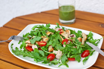 Fresh salad with rucola tomatoes and chicken breast