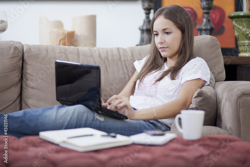Cute young woman working in her couch
