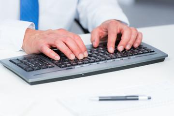 geschäftsmann schreibt auf einer computertastatur