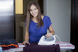 Happy young woman ironing clothes