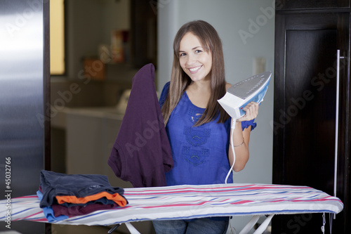 Happy housewife ironing clothes
