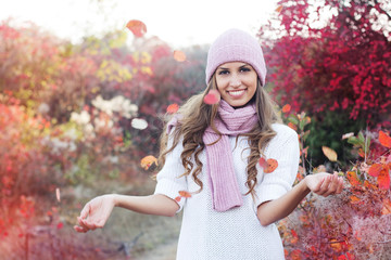 Young beautiful woman in colourful autumn leaves