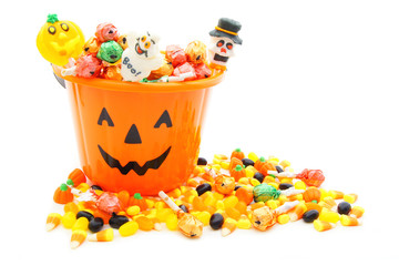 Jack-o-lantern candy pail with a pile of Halloween candy