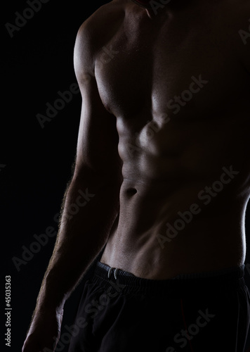 Closeup on muscular male torso with abdominal muscles on black
