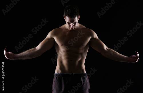 Strong muscular man posing on black