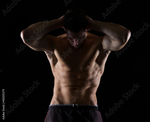 Strong male athlete posing on black
