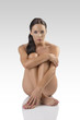 naked brunette sitting on a floor with crossed foots