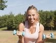 Sport au parc - Portrait d'une jeune femme soulevant des poids