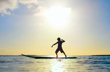 Silhouette of a boy on surfboard