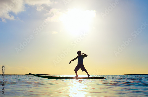 Silhouette of a boy on surfboard