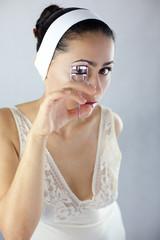 Kobieta używająca zalotki do podkręcenia rzęs