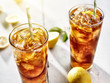 cold iced tea with straws and lemon slices in summer sun.