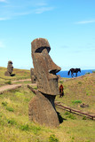 Wild horses next to moai in Rano Raraku