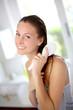 Portrait of smiling girl brushing her hair