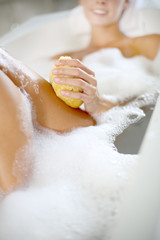 Closeup of woman using bath sponge in bathtub