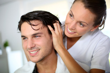 Hairdresser doing head massage to customer