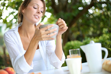 Portrait of beautiful woman having breakfast outside