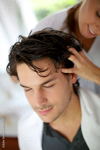 Hairdresser doing hair massage to customer