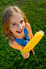 Healthy food - lovely girl eating corn on the cob