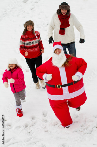 Chasing Santa Claus - happy family enjoying Christmas