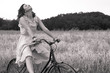 Beautiful black and white image of young woman riding bike