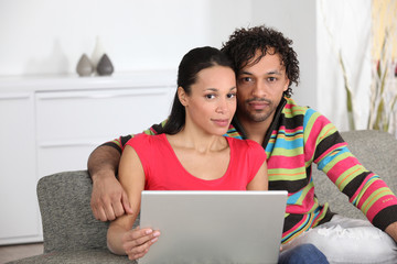 Mixed couple at home with laptop