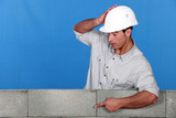 Builder pointing at a block wall