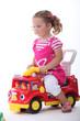 Little girl sat on toy truck