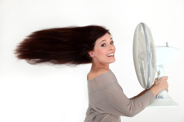 Woman with an electric fan
