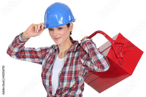 Female manual worker carrying tool box