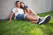 Teenage couple sitting on grass
