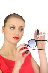 Woman choosing a pair of sunglasses