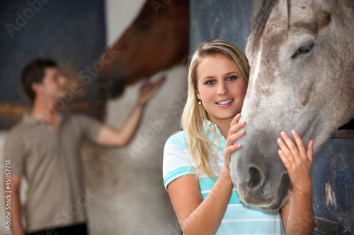 Young woman stroking her horse