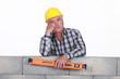Bored tradesman holding a spirit level