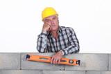 Bored tradesman holding a spirit level poster