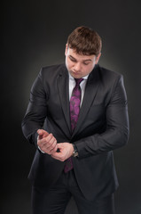 A young man in a suit corrects cufflinks
