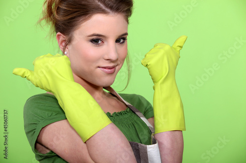 Young women wearing rubber gloves and apron