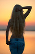 Beautiful young woman posing at the beach at sunset.
