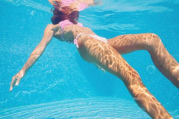 Underwater woman portrait in swimming pool.