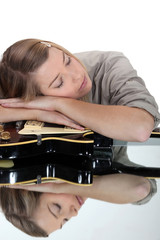 young woman asleep over her guitar
