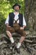 Seated man in traditional Bavarian costumes in forest