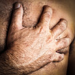 Hand grabbing the chest of a man who is suffering a heart attack
