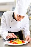 Fototapety Köchin in Restaurant oder Hotel Küche beim kochen