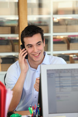 Male office worker speaking to customer on the telephone
