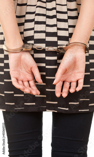 hands of a young woman in handcuffs