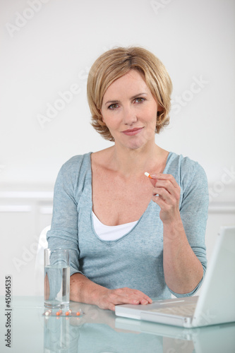A woman about to take a pill and working with computer.